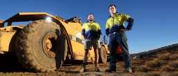 Link to Commercial Photography gallery showing two men standing in a construction site next to an earth mover