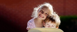 Link to freelance photography gallery showing two children peeking over a chair in a candid style