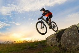 A mountain bike rider jumps off rocks with the sunset behind him