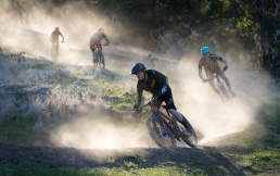 A group of 4 mountain bike riders kick up dust along the trail near Wodonga
