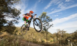 Mountain bike rider wearing green and orange jumps through the air