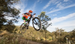 A mountain bike rider flies through the air with a blurry background