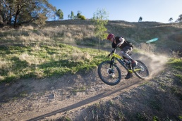 A mountain bike rider pops a mono while negotiating a berm