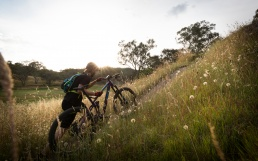A mountain bike rider pushes his bike up a steep grassy slope near Wodonga