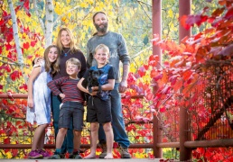 Family portrait of two adults and three children standing on a blacony surrounded by autumn leaves