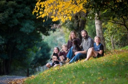 Family portrait of 5 people sitting on a hilllside under Autumn leaves