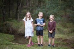 Three siblings having fun nextr to a creek