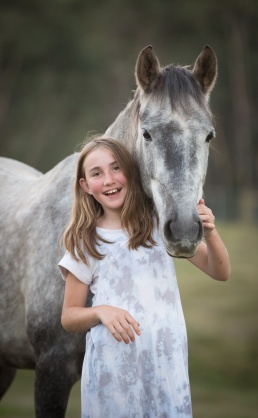 Young girl posing with horse over her shoulder