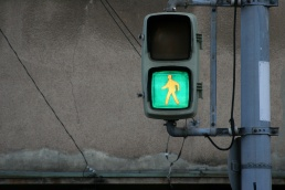 A phptpgraph of a green walk sign in front of a wall