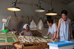 Three ladies in a Japanese fish market with fish drying on racks