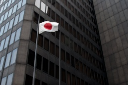 A japanese flag flies in front of the dark sides of a skyscraper