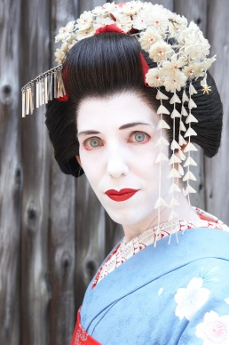 A western woman with blue eyes dressed up as a traditional Japanese geisha