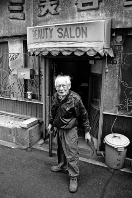 An old man stands in front of the door to a Beauty Salon in Osaka Japan