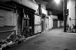 A black and white photograph of a quiet residential street at night in Tennoji Japan.