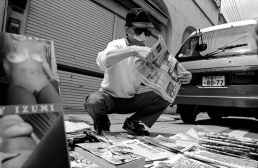 A Japanese man wearing a dust mask sells newspapers and magazines on the street Tennoji Japan