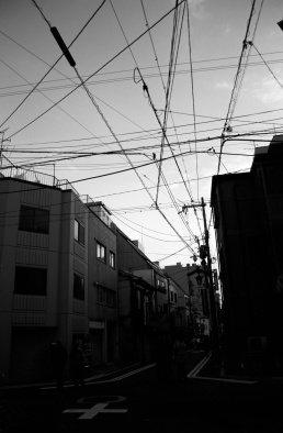 a black and white photography of electricity wires above a Japanese street