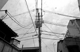 A photo pf many wires coming off a single power pole in Osaka with a plane high in the ski behind
