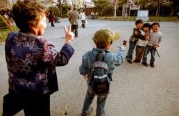 Three Japanese children pose for a photo taken by another child with a grandmother gesturing